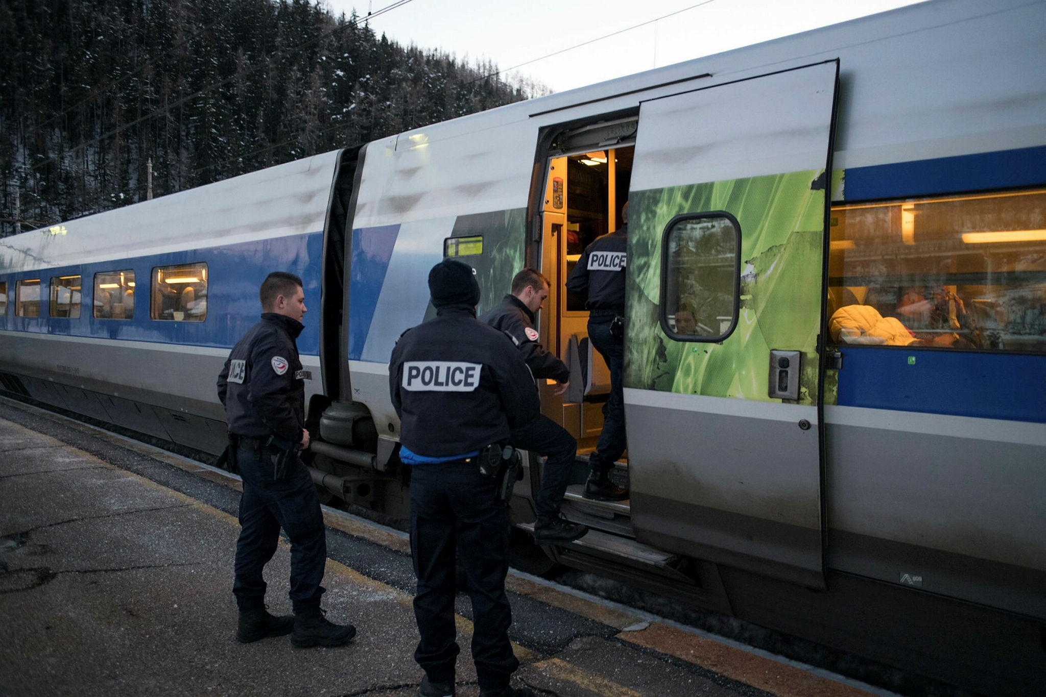 French police officers board a TGV train bound from Milan to Paris to inspect passengers and look for illegal immigrants, Jan. 12.