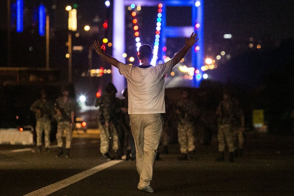 A civilian approaches Gu00fclenist putschist officers with his hands up at the entrance to the July 15 Martyrs Bridge, in Istanbul on the night of July 15, 2016 when Gu00fclenist terrorists attempted a deadly coup, killing 249 people and wounding thousands.