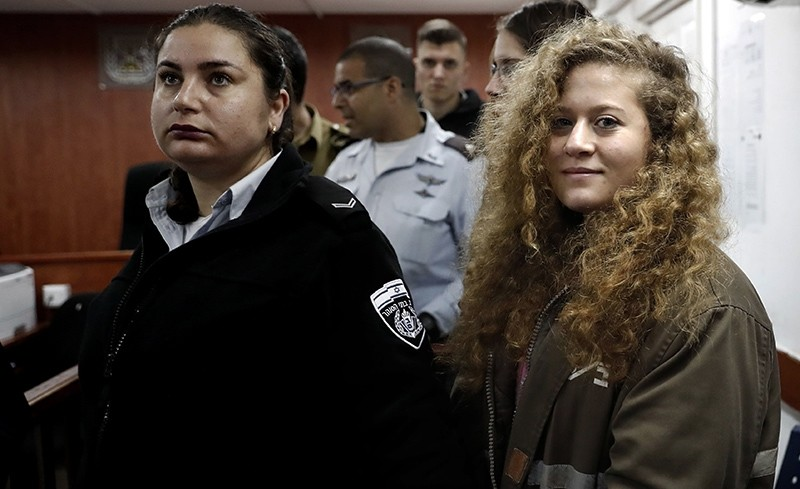17-year-old Palestinian Ahed Tamimi, right, stands for the beginning of her trial in the Israeli military court at Ofer military prison in the West Bank village of Betunia, Feb. 13, 2018. (AFP Photo)