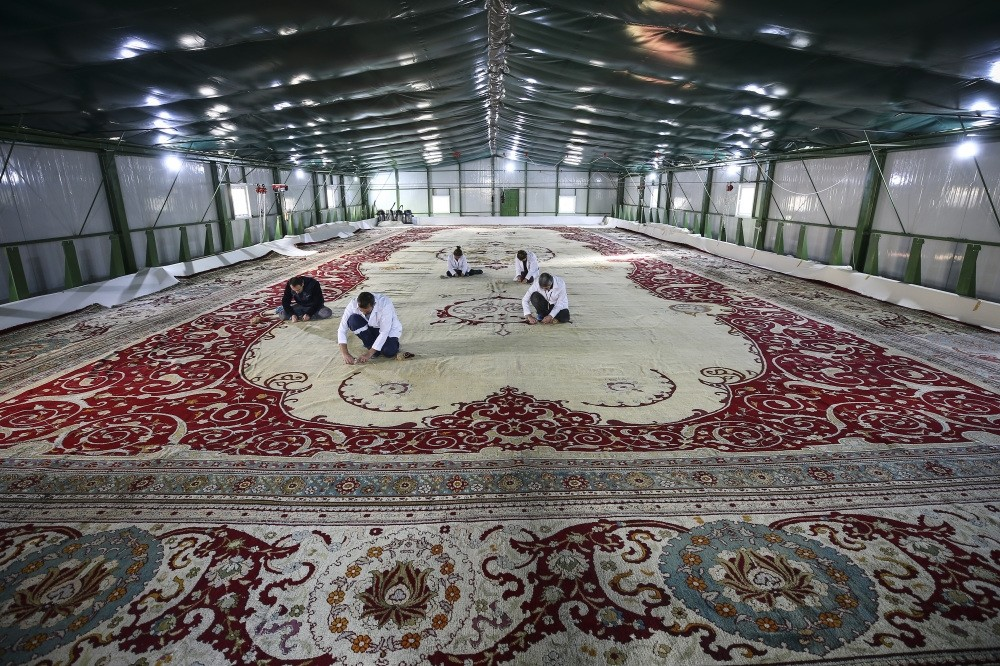 Restoration crew works on the 120-year-old carpet in a warehouse set up in the courtyard of Yu0131ldu0131z Chalet.