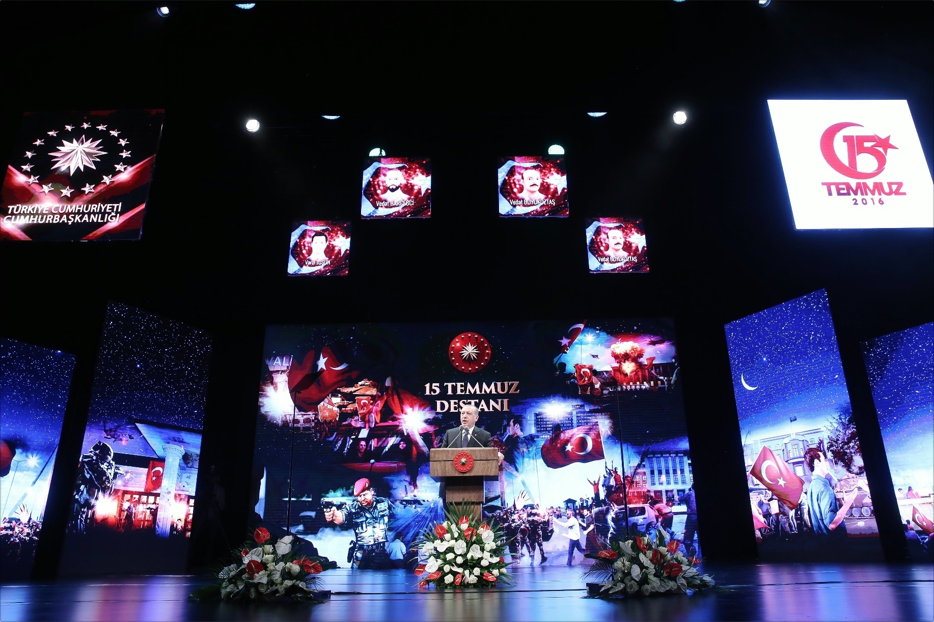Erdou011fan addresses the audience against a backdrop of photos of those who died during the coup attempt.