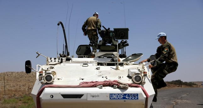 U.N. Disengagement Observer Force (UNDOF) climb onto an APC after they crossed the border from Syria to Israel at the Israeli-occupied Golan Heights side, July 26, 2018. (Reuters Photo)