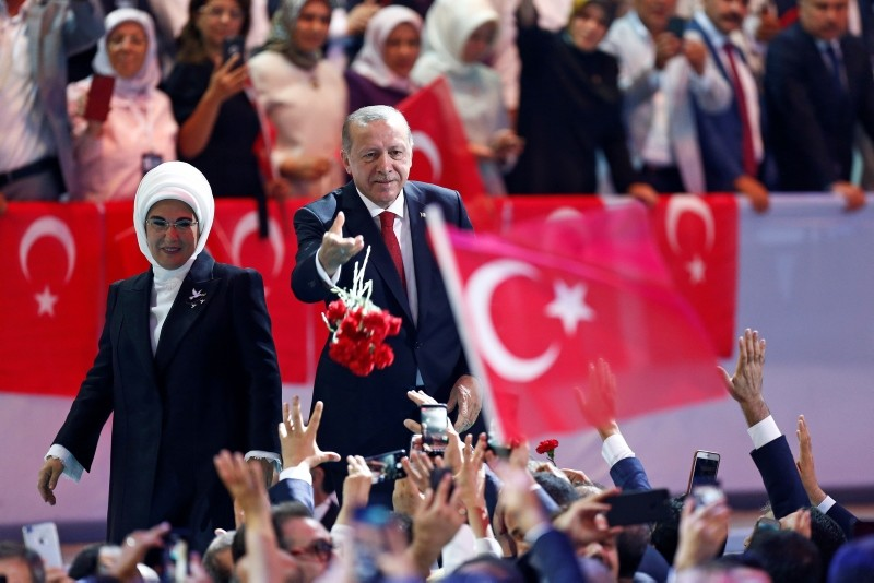 Turkey's President Recep Tayyip Erdou011fan, accompanied by his wife Emine, throws flowers to his supporters as he arrives to deliver a speech at his ruling Justice and Development Party (AK Party) convention in Ankara, Turkey, Aug. 18, 2018. (AP Photo)