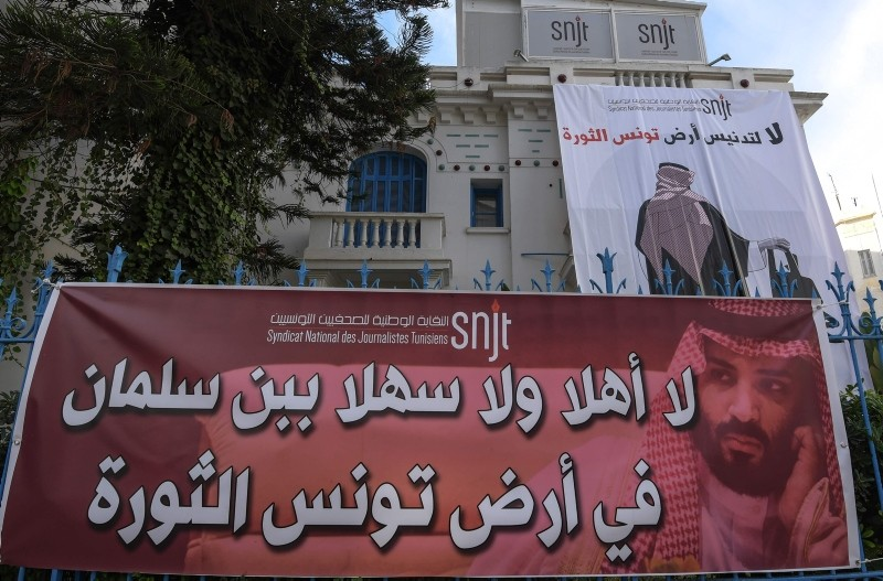 Banners hanging outside Tunisia's Journalists Union in Tunis depicting MbS with captions reading in Arabic ,no welcomes to bin Salman in Tunisia, the land of the revolution,, ,no to the desecration of Tunisia, the land of the revolution,. (AFP Photo)