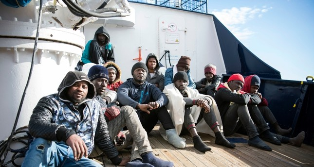 Migrants sit on the deck of the Sea-Eye rescue ship in the Mediterranean Sea, Tuesday, Jan. 8, 2018. (AP Photo)