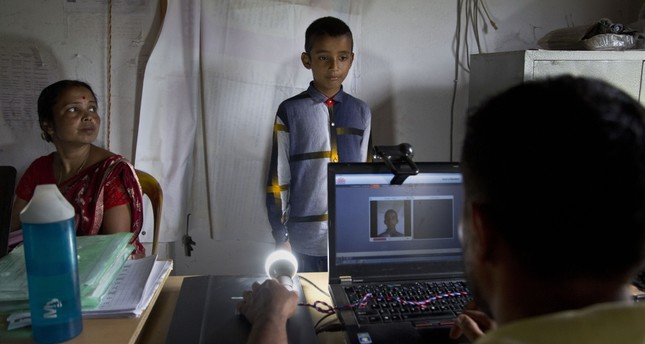 A National Register of Citizens (NRC) officer takes a photograph of a boy at an NRC center, Gauhati, Aug. 30, 2019.