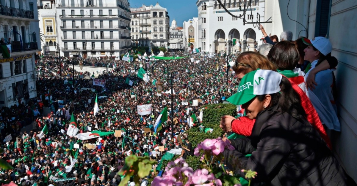 Algerians look down from a balcony upon protesters gathering during a mass demonstration against ailing President Abdelaziz Bouteflika in the capital Algiers on March 29, 2019. (AFP Photo)