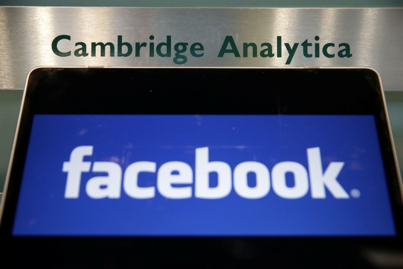 In this file photo taken on March 21, 2018 A laptop showing the Facebook logo is held alongside a Cambridge Analytica sign at the entrance to the building housing the offices of Cambridge Analytica, in central London. (AFP Photo)