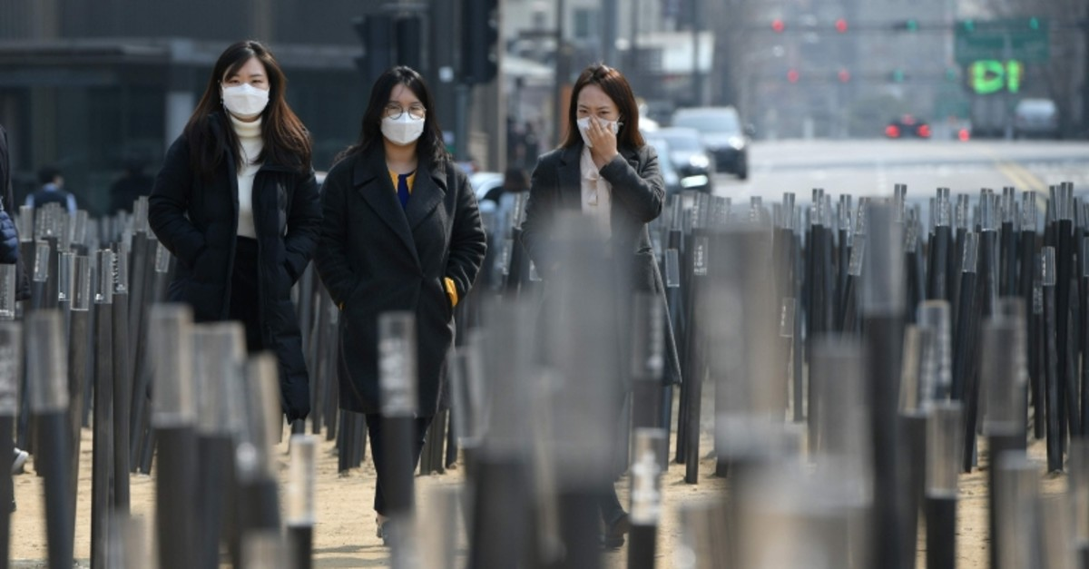 Pedestrians wearing face masks walk through a park during heavily polluted weather in Seoul on March 4, 2019. (AFP Photo)