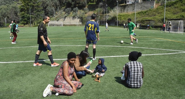 Women migrants Eunice (L) from Nigeria and Hawa (R) from Gambia relax along the pitch as migrants play football with a local team in Sant' Alessio in Aspromonte, a small village of 330 inhabitants in Calabria.