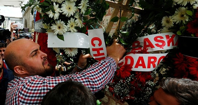 A mourner brings down a wreath from CHP's Kılıçdaroğlu during a funeral ceremony for the police officers who were killed in Tuesday's car bomb attack on a police bus, in Istanbul, Turkey, June 8, 2016. (Reuters Photo)