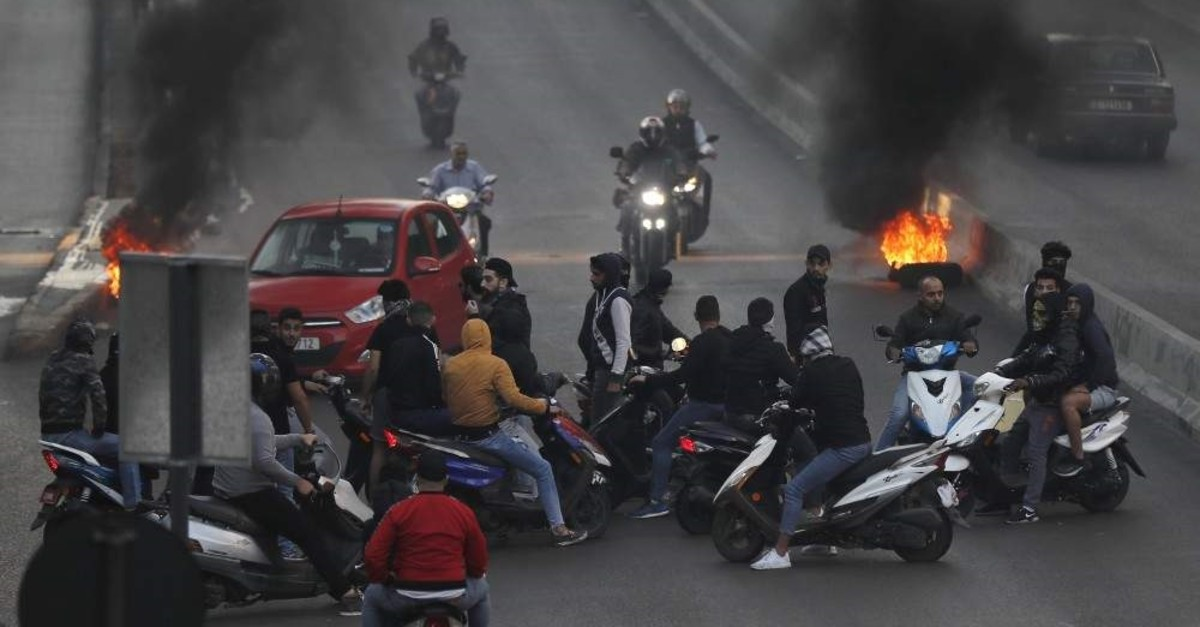 Anti-government protesters on their scooters block a main highway that links to the airport by burned tires, during ongoing protests against the Lebanese government, in Beirut, Lebanon, Monday, Nov. 4, 2019. (AP Photo)