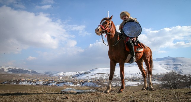 A Kyrgyz man traditional clothing rides a horse.