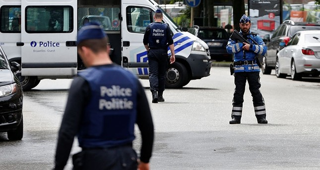 Belgian police officers stand guard near an apartment building during the reconstruction of the recent attacks, in the Brussels district of Etterbeek, Belgium, June 17, 2016. (Reuters)