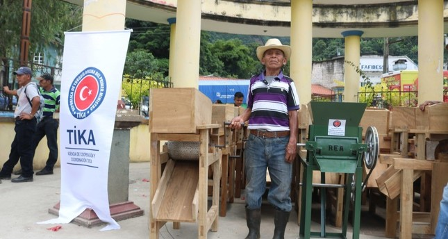 A Mayan farmer poses with equipment donated by TİKA.
