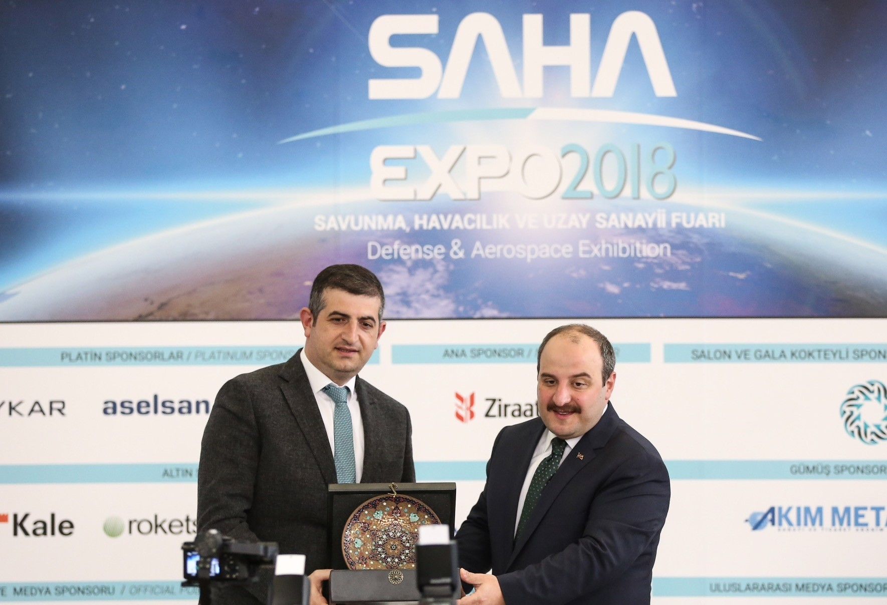SAHA Chairman and General Manager of Baykar Makine  Haluk Bayraktar (L) hands a crest to Industry and  Technology Minister Mustafa Varank (R) shake hands at the opening ceremony of SAHA EXPO 2018 in Istanbul, Sept. 13.