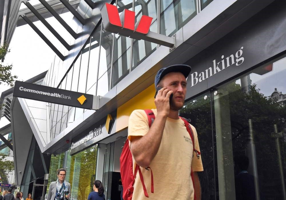 A man walks past a branch of a Westpac and Commonwealth banks in Melbourne, Feb. 4, 2019.