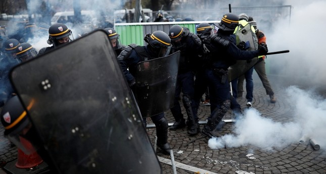 Police officers fire a tear gas during a Yellow vest protests against higher fuel prices, on the Champs-Elysees in Paris, France, November 24, 2018. (Reuters Photo)