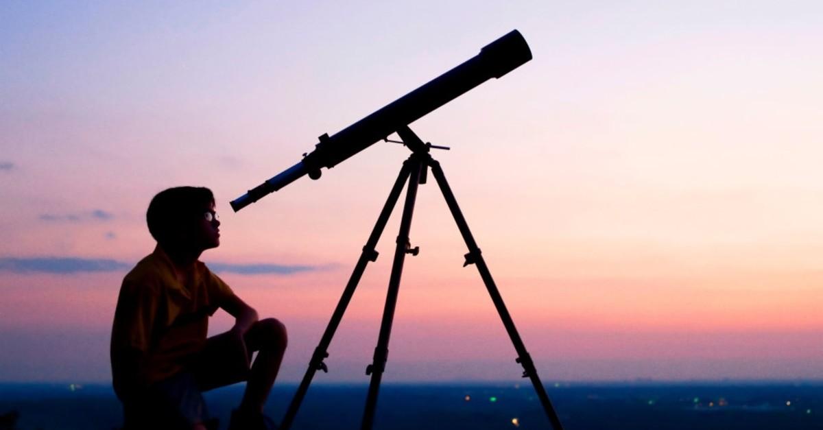 A boy gazes the stars with a telescope.