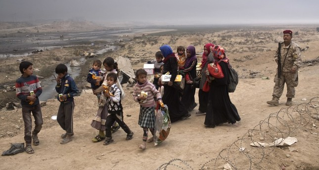 Internally displaced persons clear a checkpoint in Qayara, some 50 kilometers south of Mosul, Iraq, Oct. 26, 2016.