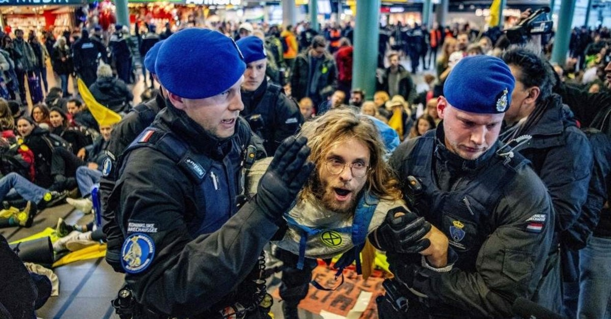 Royal Dutch police officers escort a Greenpeace activist during a protest to denounce airline pollution in the main hall of the Amsterdam Schiphol airport on December 14, 2019. (AFP Photo)