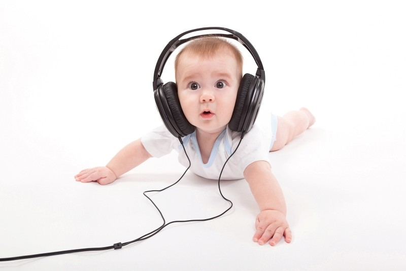 Charming baby on a white background, listening to music  with headphones. (FILE Photo)