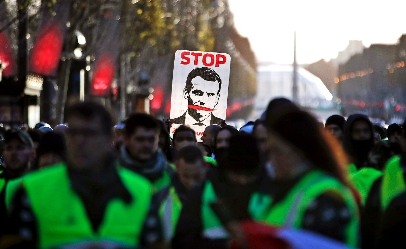 ,Yellow vests, protesters hold a sign saying ,Stop Macron, as they walk down the Champs Elysees avenue to Place de la Concorde during a demonstration in Paris, Dec. 8.
