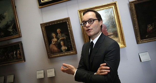 Head of the paintings department at the Louvre museum, Sebastien Allard, answers reporters next to paintings looted by Nazis during World War II, in Paris, Tuesday, Jan. 30, 2018. (AP Photo)
