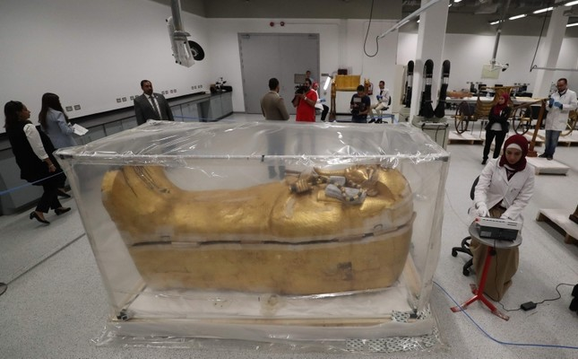 The gold-covered sarcophagus of King Tutankhamun's coffin is encased in a tent for restoration procedures at the conservation center of the the Grand Egyptian Museum in Giza, near Cairo, Egypt, Sunday, Aug. 4, 2019. AP Photo