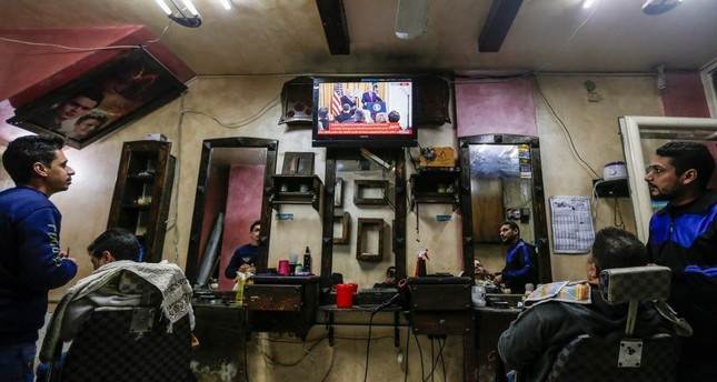 Palestinians watch the televised press conference of U.S. President Donald Trump and Israeli Prime Minister Benjamin Netanyahu at a barber shop in Gaza City, Jan. 28, 2020. AFP Photo