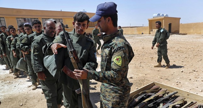 SDF forces receive weapons during their graduation ceremony, at Ain Issa desert base, in Raqqa province, northeast Syria, Thursday, July 20, 2017. (AP Photo)