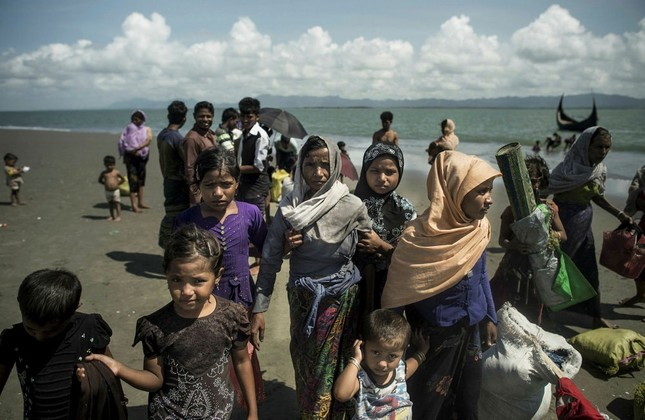 Rohingya Muslim refugees walk on the Bangladeshi shoreline of the Naf River after crossing the border from Myanmar in Teknaf on Sept. 30.