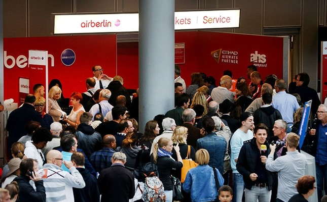 Flight passengers crowd in front of the desk of German airline Air Berlin at the airport in Duesseldorf, western Germany, on September 12, 2017, after the troubled airline had to cancel flights due to operational reasons. (AFP Photo)