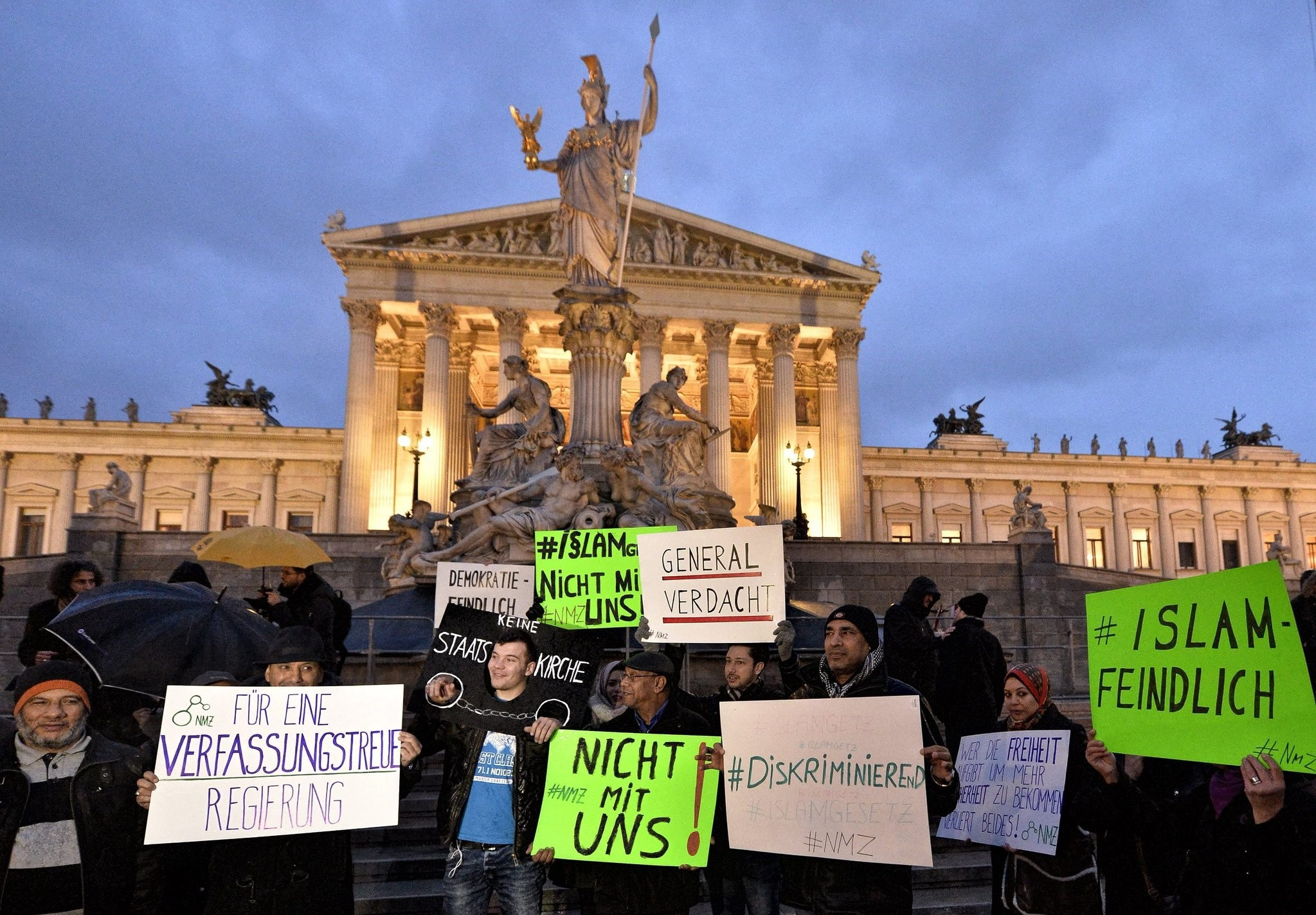 Protesters hold banners during the demonstration under the slogan 'New Islam Law? Not with us!' in front of the parliament building in Vienna (EPA File Photo)