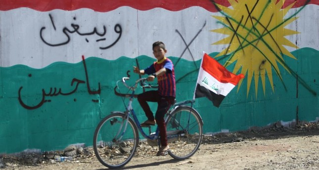 A boy rides a bicycle flying the Iraqi national flag past a wall mural depicting the KRG flag in the area of Dibs, west of Kirkuk on Oct. 17, 2017.