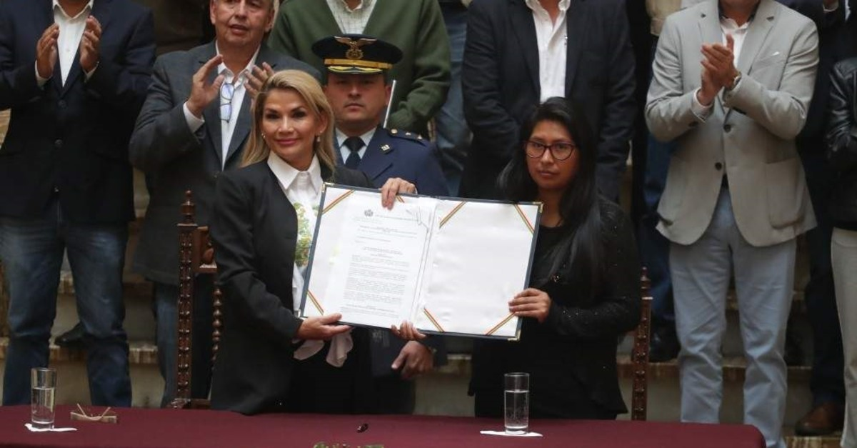 The interim president of Bolivia, Jeanine Anez (L), shows a document with President of Senate Monica Eva Copa (R) surrounded by members of her Cabinet, at the Government Palace in La Paz, Bolivia, Nov. 24, 2019. (EPA Photo)