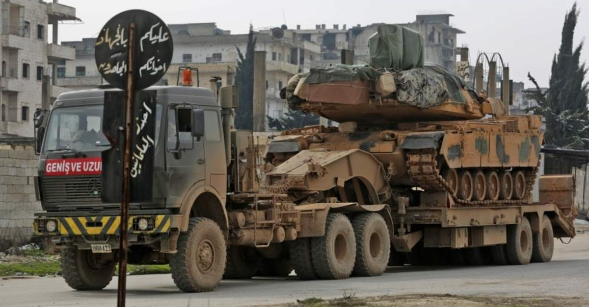 A Turkish military tank is towed as a convoy passes along the M4 motorway by the town of Ariha, about 13 kilometers south of Idlib in the northwestern Syrian Idlib province Feb. 14, 2020. (AFP Photo)