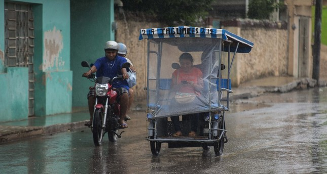 Inhabitants of Tzubcacab, in the Mexican state of Yucatan drive their vehicles during rain from tropical storm Earl, in Mexico, on 05 August 2016. (EPA Photo)