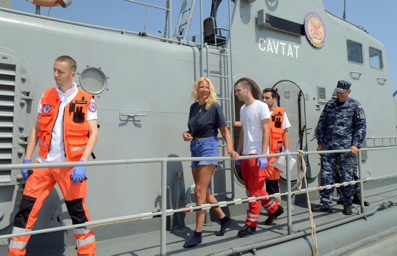 In this photo taken Aug. 19, 2018, a woman who identified herself as Kay from England, center, is escorted by rescuers from a Croatian Coast Guard vessel in the port in Pula, Croatia. (AP Photo)