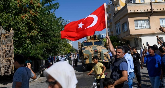 A man waves a Turkish flag as Turkey-backed Syrian opposition fighters enter Tel Abyad from the Turkish gate towards Syria in Akçakale in Şanlıufa province on October 10, 2019. (AFP Photo)