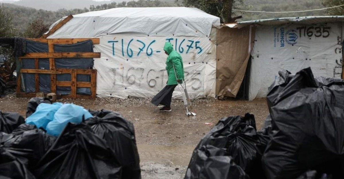A migrant makes his way during heavy rainfall at a temporary camp for refugees and migrants next to the Moria camp on the island of Lesbos, Feb. 6, 2020. (REUTERS Photo)