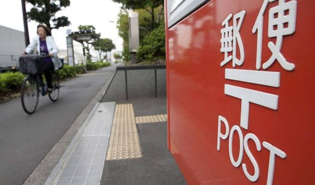 A pedestrian cycles near a post box outside a Japan Post Network Co. branch in Tokyo, Japan, on Tuesday, Oct. 30, 2012. (Tomohiro Ohsumi/Bloomberg via Getty Images)