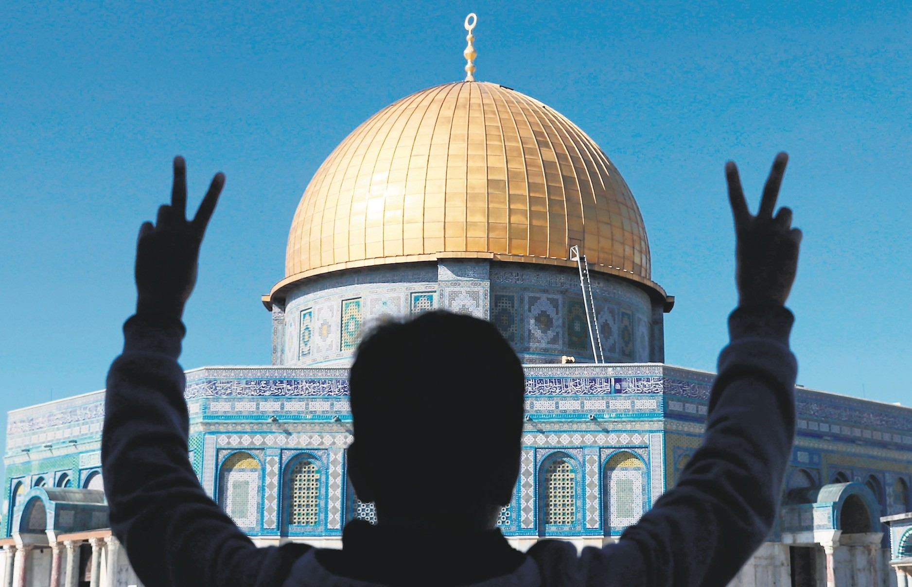A Palestinian youth flashes the u201cvictoryu201d sign after during prayers in front of the Dome of the  Rock at the Al-Aqsa Mosque compound, Jerusalemu2019s Old City, Dec. 8.