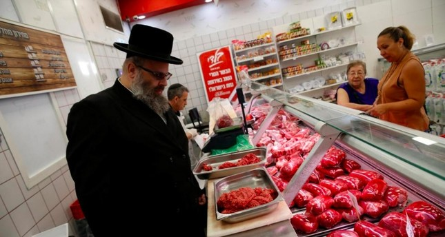 Kosher inspector Aaron Wulkan examines display refrigerators containing meat in a food store to ensure that the food is stored and prepared according to Jewish regulations and customs (Reuters File Photo)