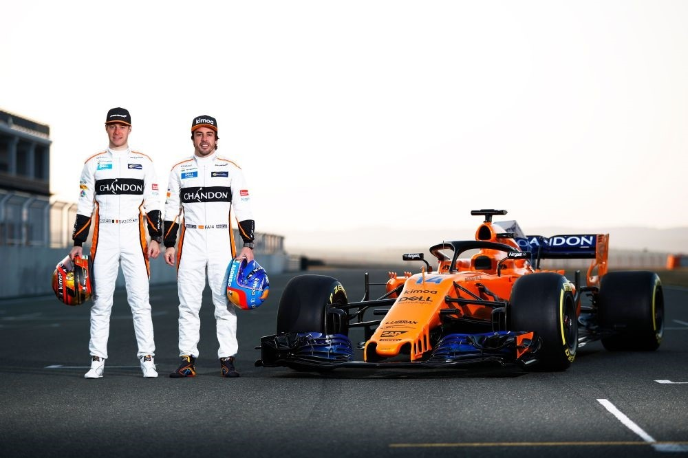 McLaren's Belgian driver Stoffel Vandoorne (L) and Spanish driver Fernando Alonso pose by the MCL33 Formula One racing car for the 2018 season.