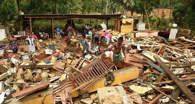 Sri Lankan residents walk among damaged homes following flooding in Yatagampitiya village in Bulathsinhala on June 2, 2017. (AFP Photo)