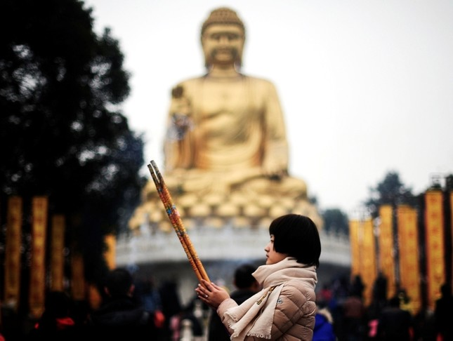 A worshipper offers prayer in front of a Buddha statue for her first visit of the year in Huayan Temple in southwest China. (AP Photo)
