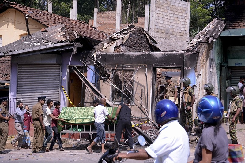 Sri Lankan police personnel stand near a vandalized building as they prepare to remove the body of a man who was killed in Digana, a suburb of Kandy, Sri Lanka, March 6, 2018. (AP Photo)