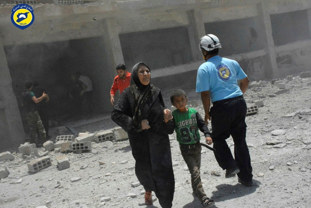 Civilians rushing out of the damaged buildings after airstrikes hit a school housing a number of displaced people,  in the southern Daraa province of Syria. (Syrian Civil Defense White Helmets via AP)