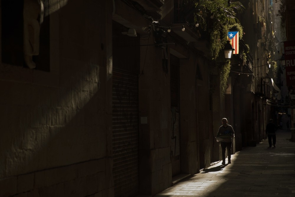 A man walks past a Catalan flag hanging off a balcony in downtown Barcelona, Oct. 24.
